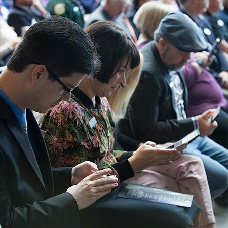 Invitados sentados con sus teléfonos celulares