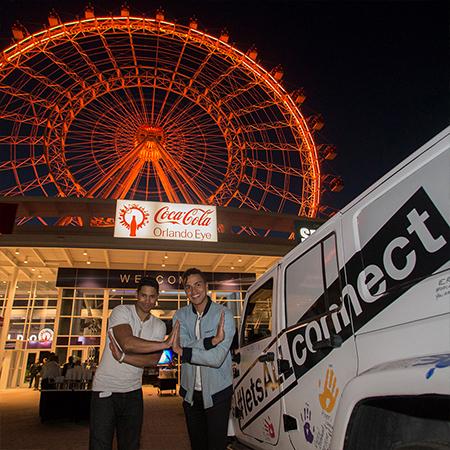 Dos hombres se saludan con la rueda de observación Orlando Eye de fondo, de noche