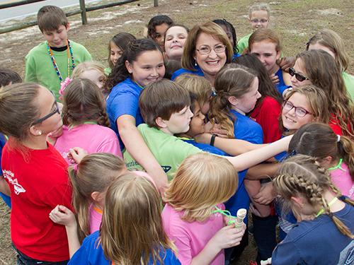 la Alcaldesa Teresa Jacobs sonriendo mientras recibe el abrazo de una decena de niños