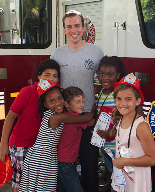 Children hugging a firefighter in front of a fire truck