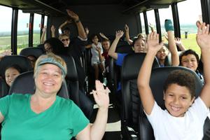 Grandes y chicos levantan las manos celebrando elDía del Reciclaje en el Condado de Orange2018durante un recorrido en autobús por el vertedero.