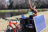 Photo of young man sitting on a solar panelled bike